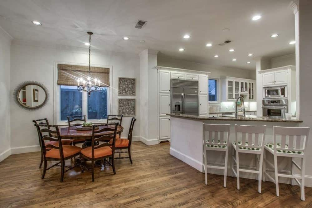 The kitchen includes an adjoining breakfast nook and an angled peninsula paired with striped counter chairs.