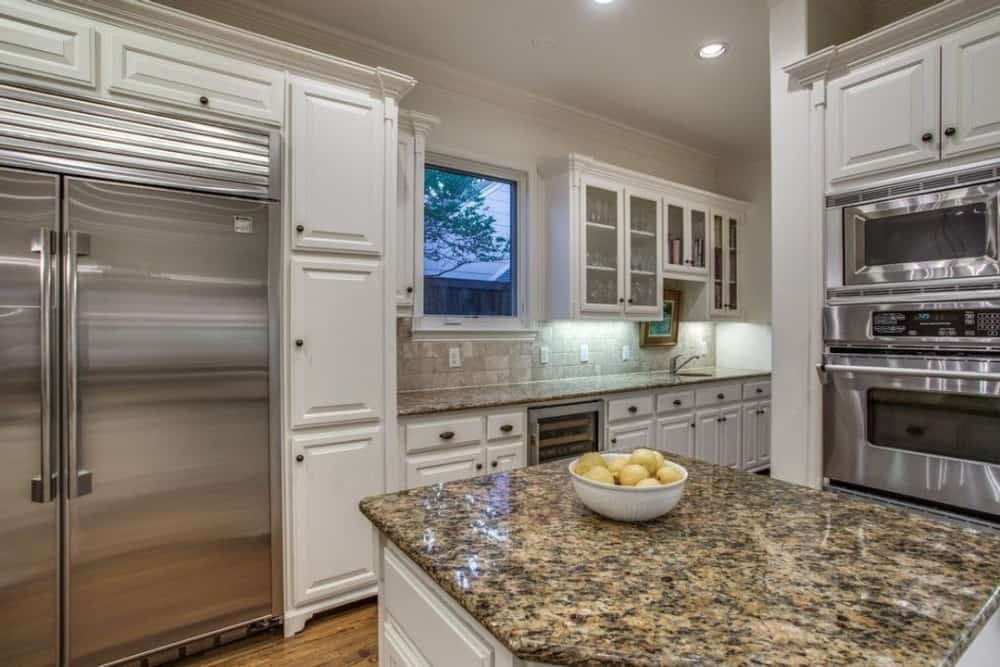 The kitchen offers white cabinetry, stainless steel appliances, a center island, and a picture window.