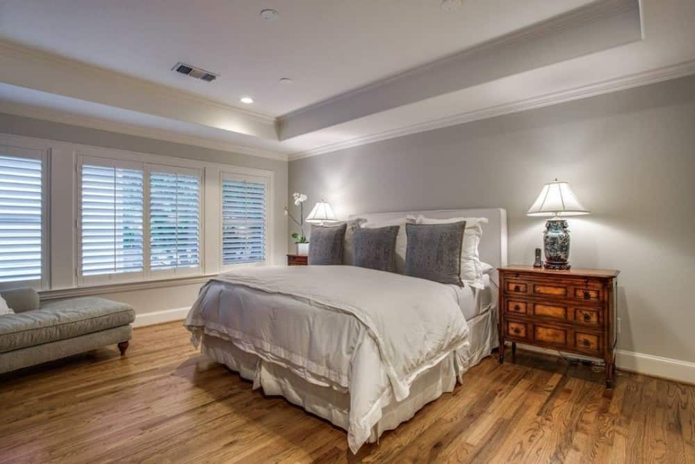 Primary bedroom with a tray ceiling, a cozy chaise lounge, and a skirted bed flanked by wooden nightstands.