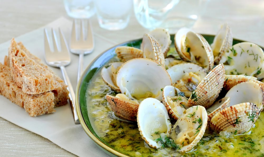 This is a close look at a bowl of steamed clams with white wine sauce and bread on the side.
