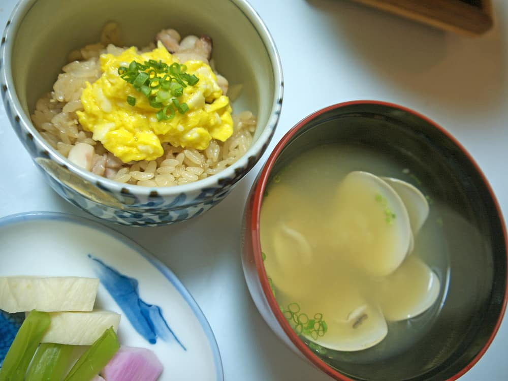This is a closed look at a Japanese lunch set that has a bowl of clam miso soup.