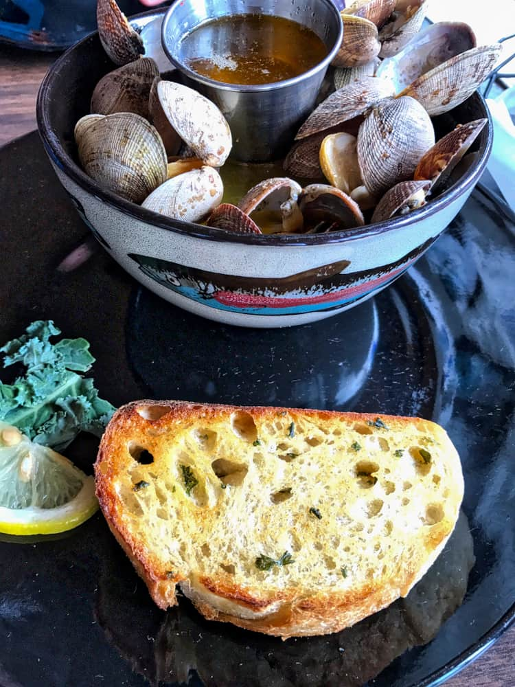 This is a bowl of steamed clams with a side of melted butter and bread.