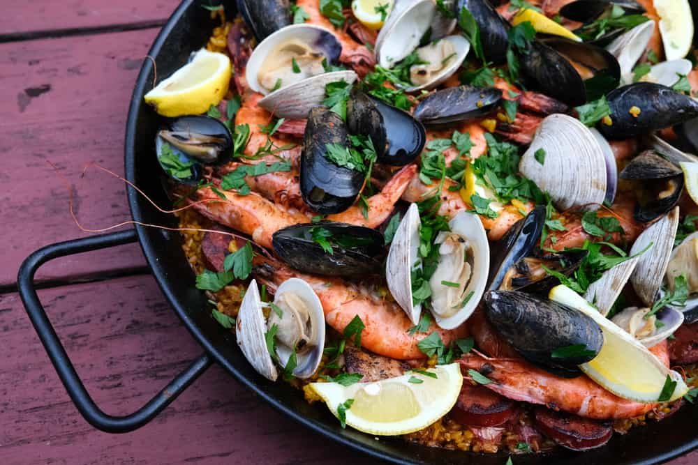This is a close look at a seafood paella with lemon on a wooden table.