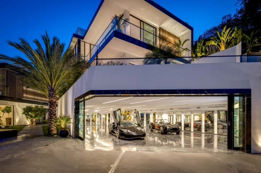 This is an exterior view of the house with bright white exterior walls, glass walls and railings and warm lighting that matches the interior and exteriors with a view of the garage that has a brightly lit interior. Image courtesy of Toptenrealestatedeals.com.