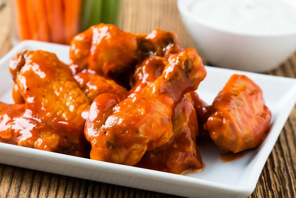 A plate of spicy buffalo chicken wings with cayenne pepper.