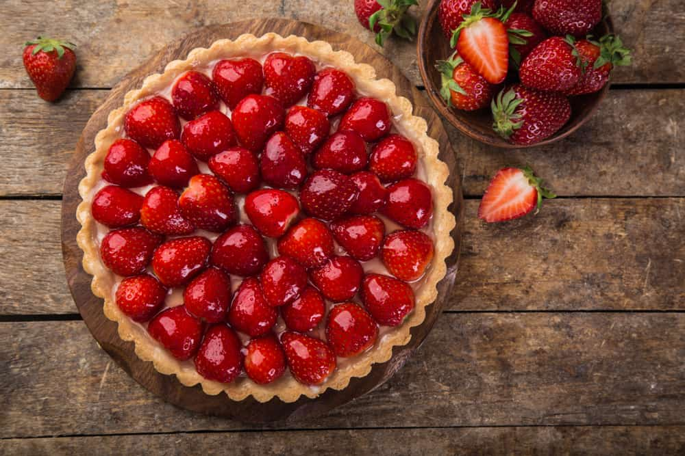 A close look at a whole fresh strawberry pie on a wooden table.