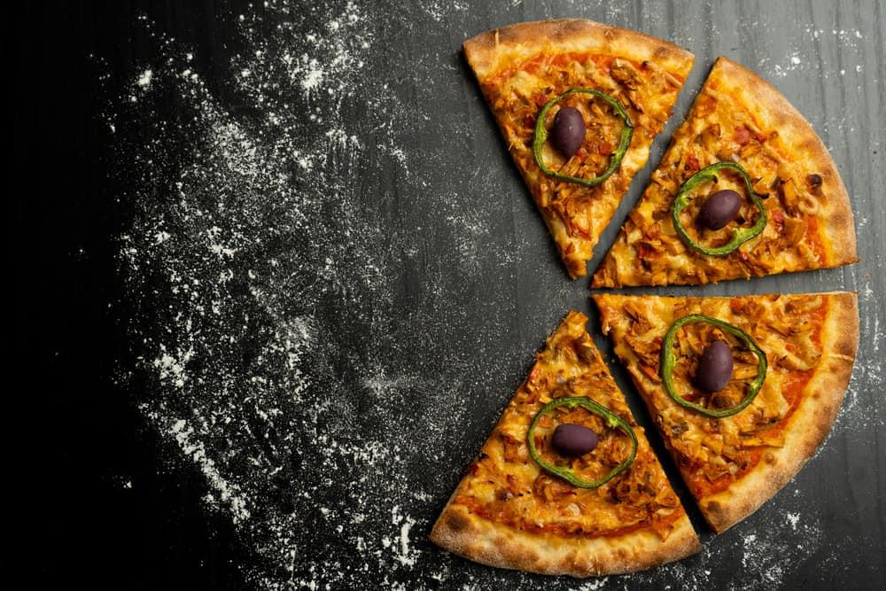 Jackfruit pizza slices on a dark table with flour.