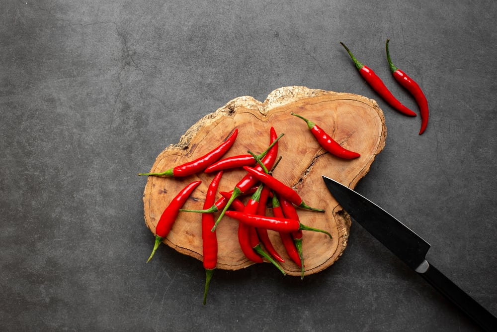 A look at a bunch of fresh red peppers on a chopping board.