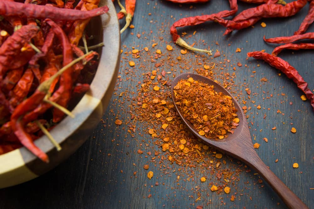 A close look at a bunch of cayenne pepper flakes on a wooden spoon.