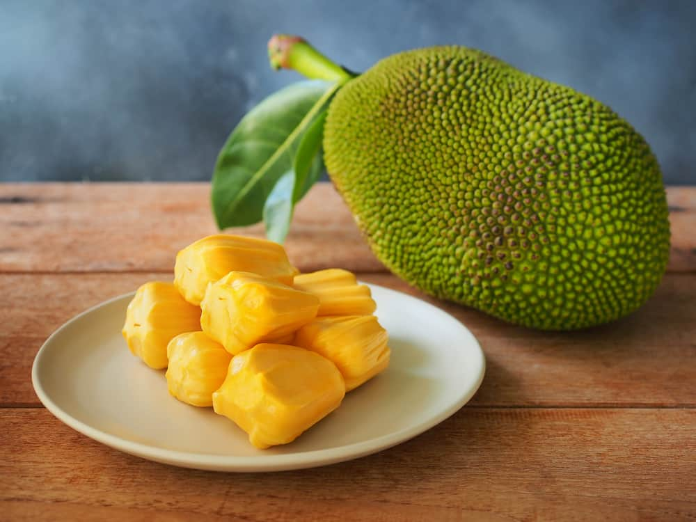 Pieces of jackfruit flesh on a white plate with a fresh fruit on the side.