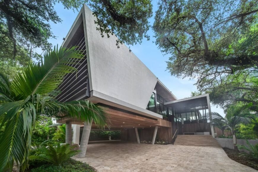 This is an exterior view of the house that has a wide driveway, a large car port under a concrete structure of the house that has glass walls.