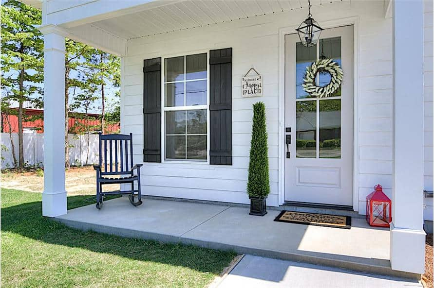 The entry porch has a dark wood rocking chair and a glazed entry door complemented with a bordered rug.