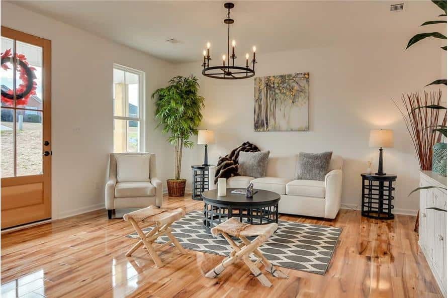 Great room with beige seats, wooden stools, and a round coffee table sitting on a patterned area rug.