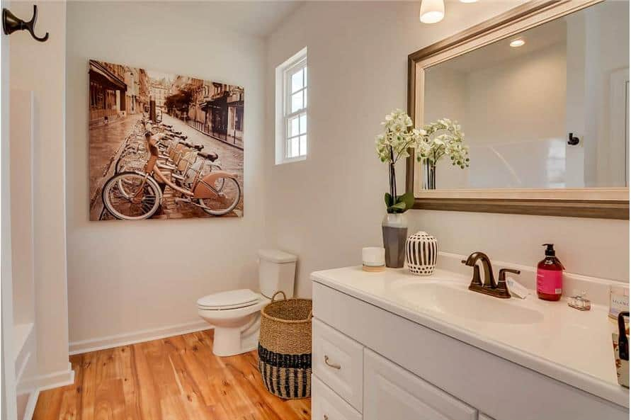 Primary bathroom with a sink vanity, a toilet, and a large artwork gracing the white walls.
