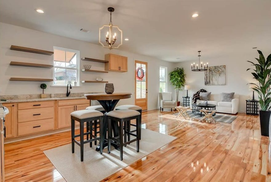 Eat-in kitchen with wooden cabinets, floating shelves, and a round dining set well-lit by a brass chandelier.