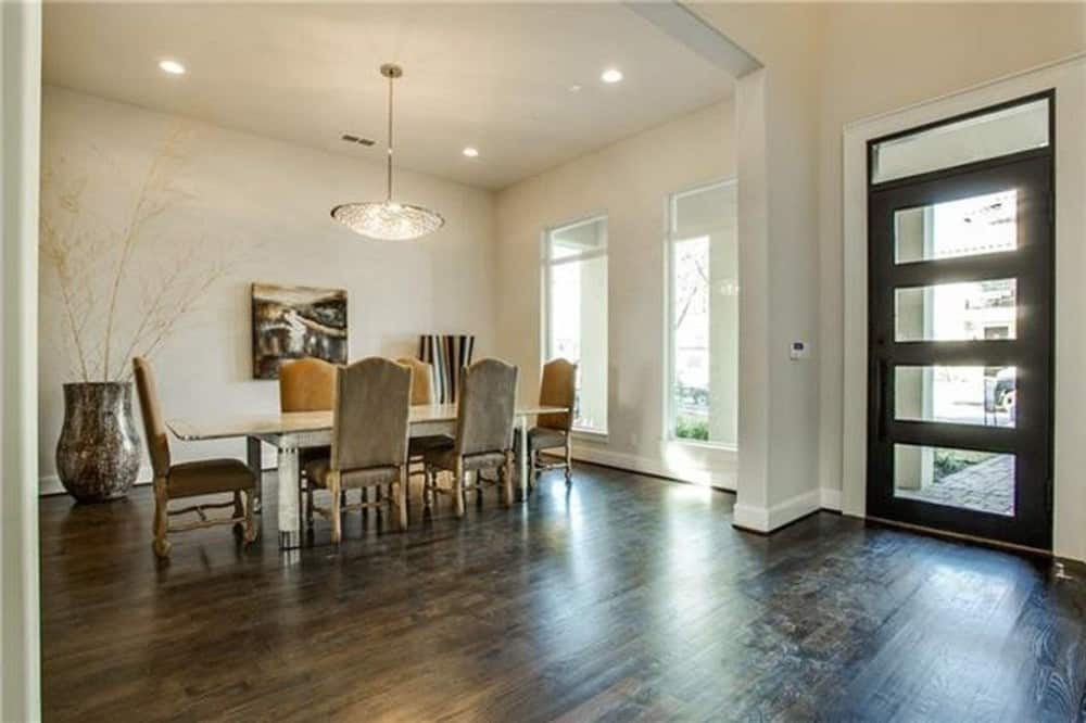 Home entry with a glazed front door and hardwood flooring. On its right is the formal dining room framed with an oversized doorway.