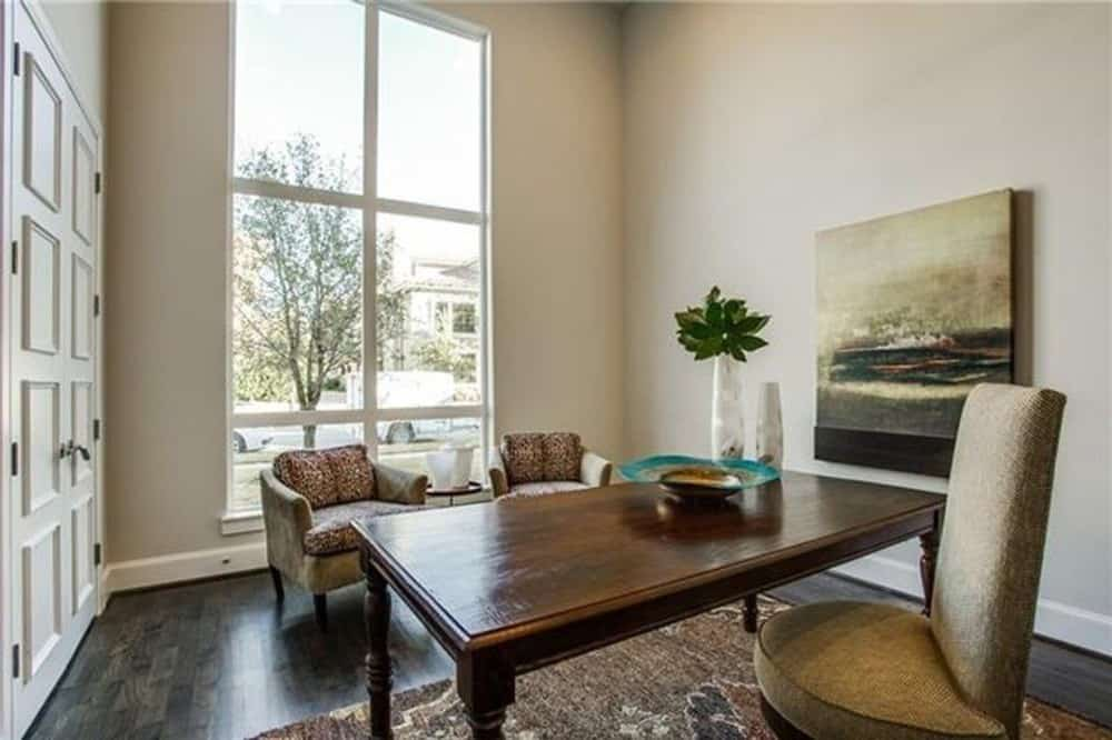 The study has a dark wood desk, comfy chairs, and a tall window that invites natural light in.