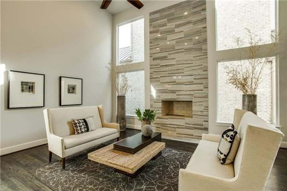 Family room with wingback sofas, a wooden coffee table, and a fireplace flanked by tall vases.