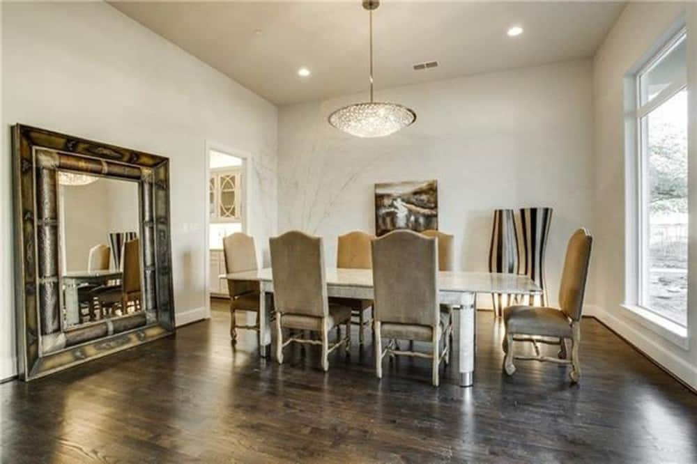 Dining room with a large decorative mirror and a 6-seater dining set well-lit by a glass dome pendant.