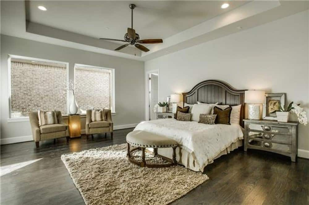 The primary bedroom features a tray ceiling, wooden furnishings, and natural hardwood flooring topped with a shaggy rug.