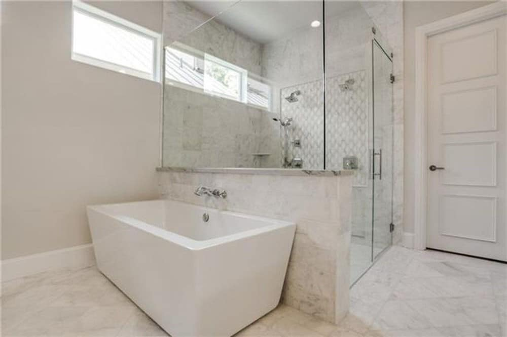 The primary bathroom includes a walk-in shower and a freestanding tub over marble tile flooring.