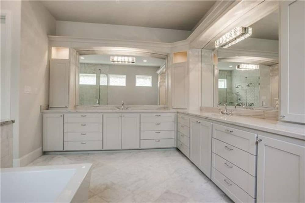 Primary bathroom with his and her sink vanities well-lit by linear sconces.
