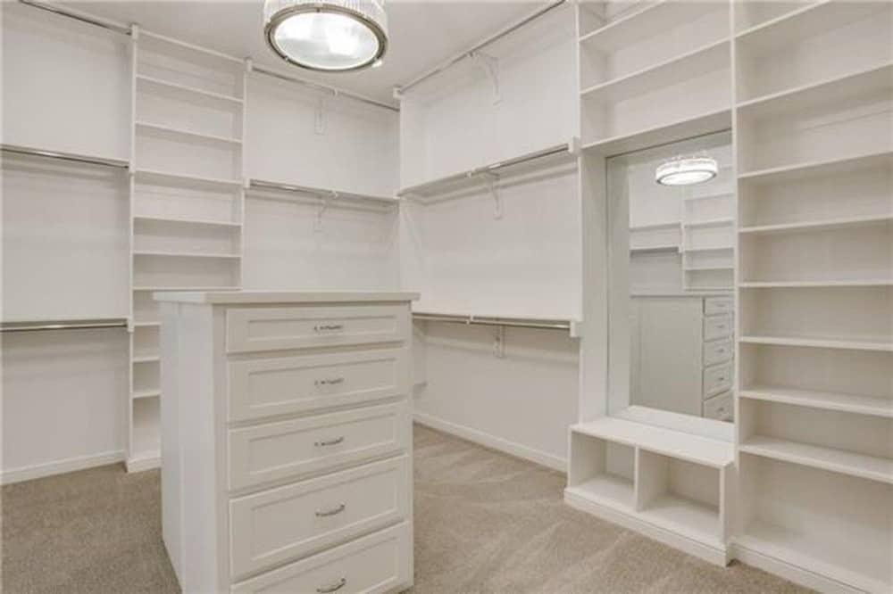 The walk-in closet is filled with white built-in shelves, a frameless mirror, and a center island.