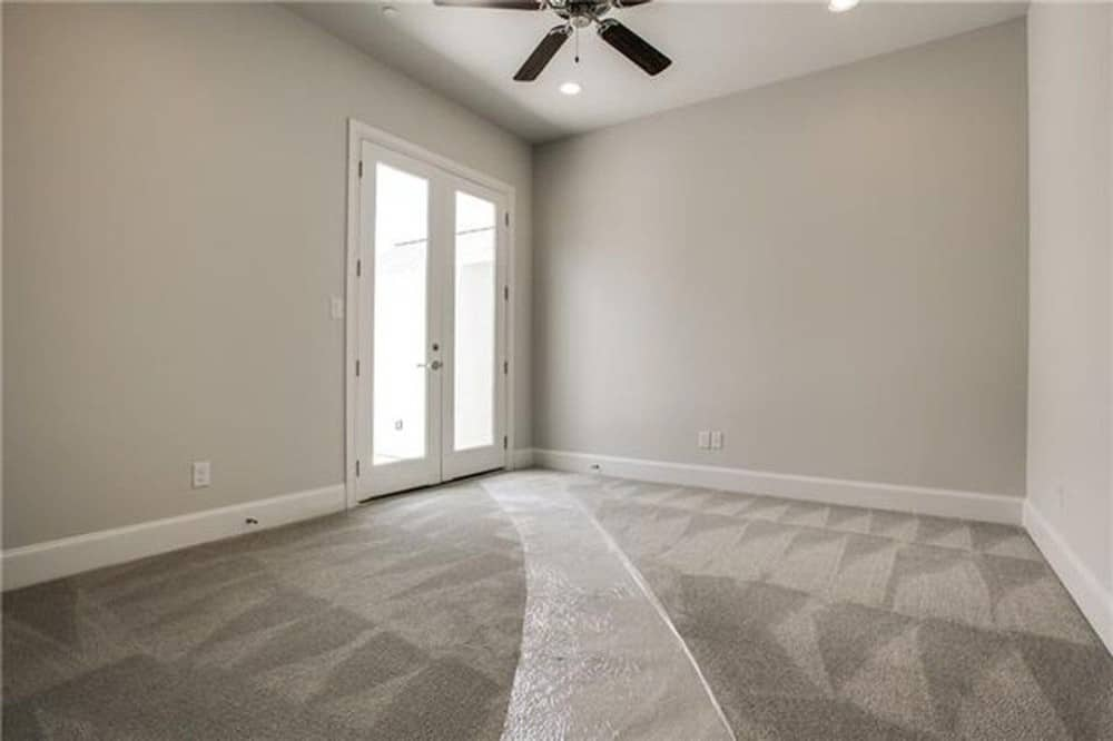 This bedroom has carpet flooring, a ceiling fan, and a french door leading to the balcony.