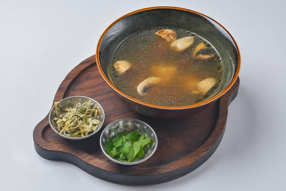 A bowl of clam base clear soup with sides.