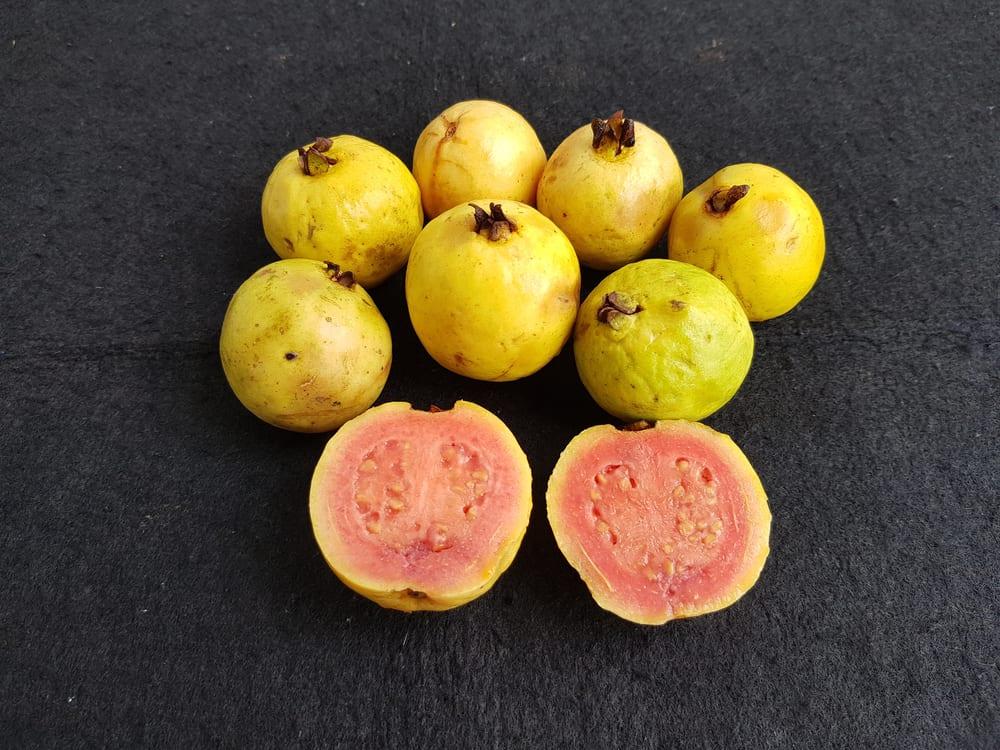 Pieces of ripe lemon guavas on a dark surface.
