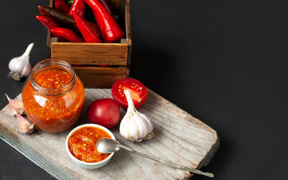 A jar of chili sauce with tomatoes and garlic.