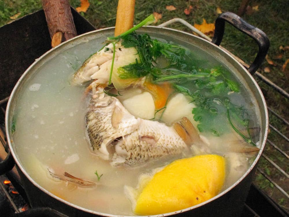 Fish soup with vegetables cooking in a pot.