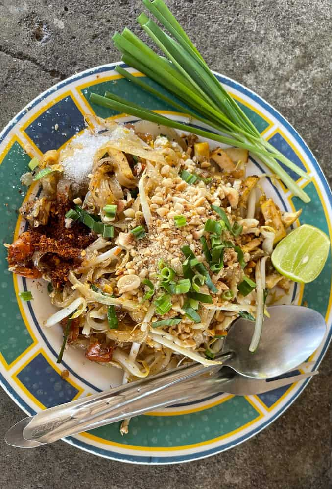 A plate of pad thai noodles with vegetables and cayenne pepper.
