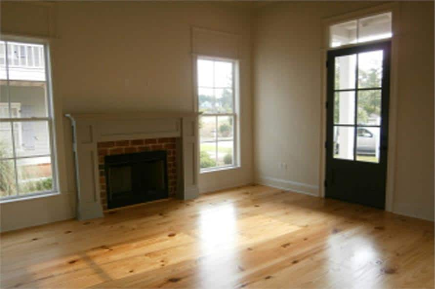 Living room with a glazed front door, hardwood floor, and a brick fireplace flanked by windows.