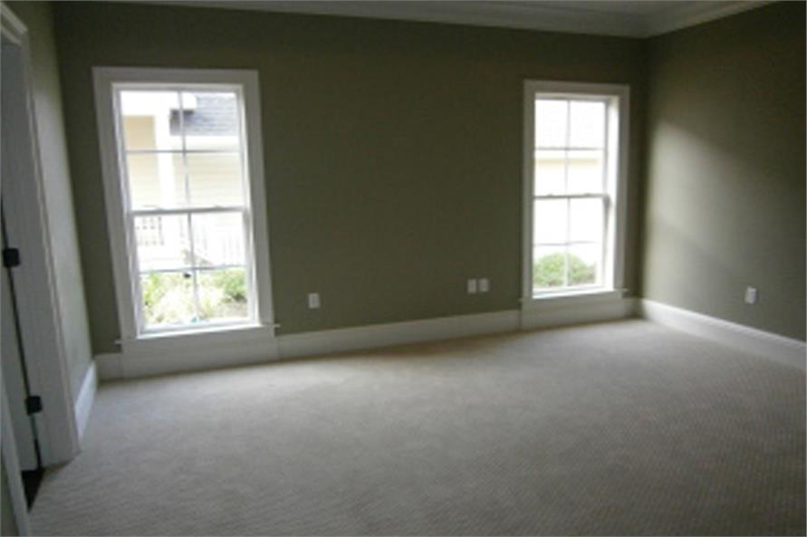 The primary bedroom has carpet flooring and gray walls lined with white moldings.