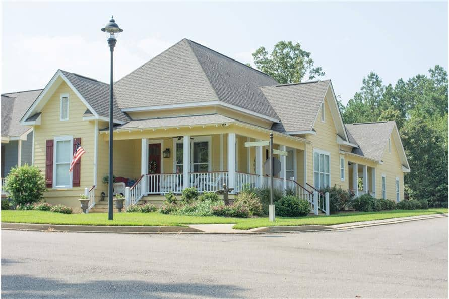 The angled front view shows the yellow siding, exposed rafter tails, and a wraparound front porch bordered by white columns and railings.