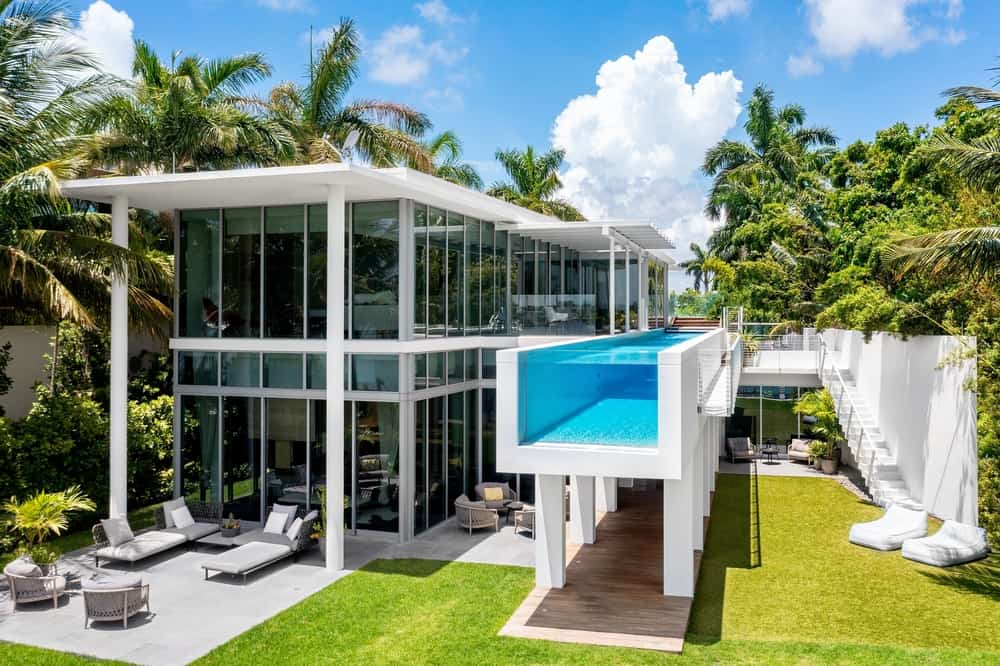 This is an aerial view of the back of the house showcasing large glass walls on two levels and a floating infinity pool on the upper level. Image courtesy of The Carroll Group at Compass.