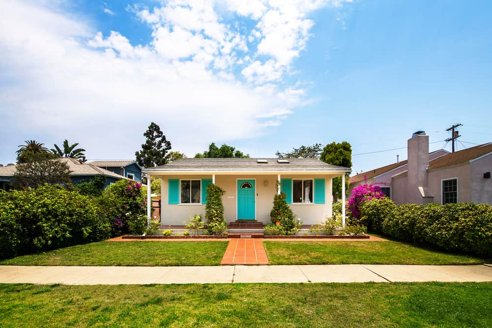 This is a front exterior view of the house showcasing a large front lawn that has grass, walkway and exterior walls complemented by the pastel accents. Image courtesy of Toptenrealestatedeals.com.