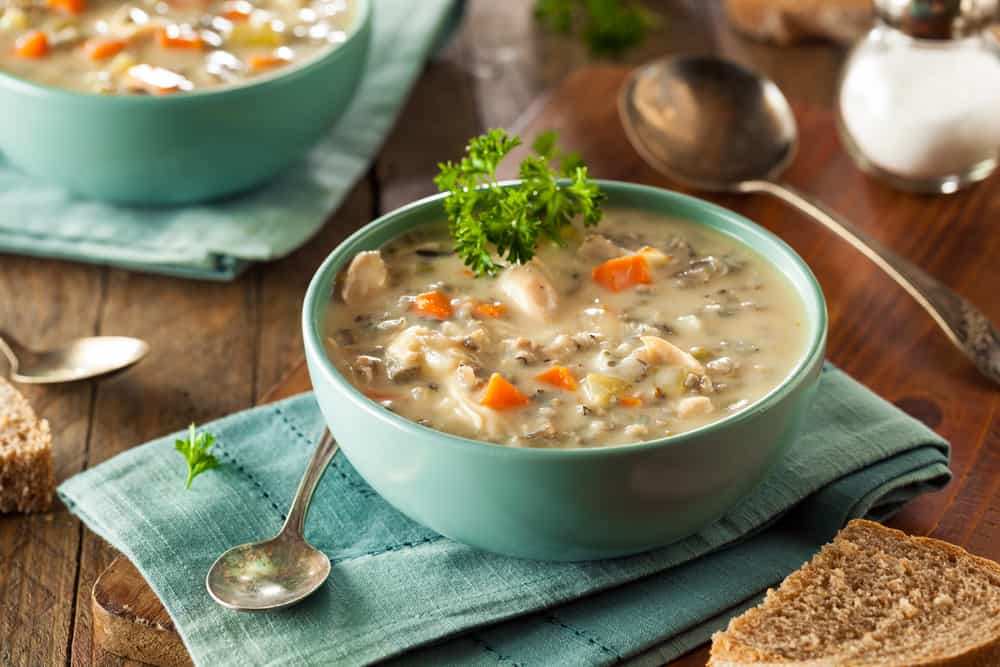 A bowl of creamy chicken soup with pasta and a side of bread.