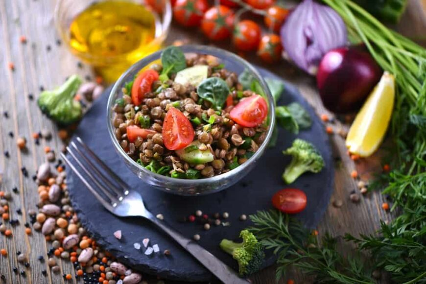 A bowl of lentil salad with ingredients around it.