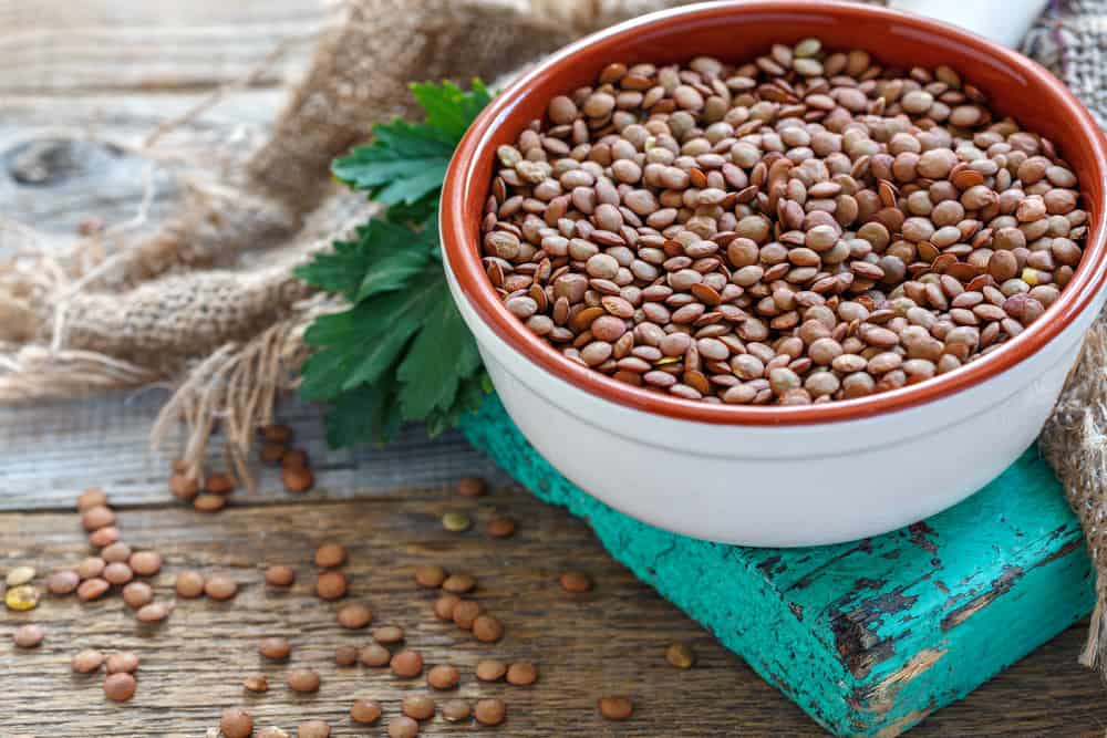 This is a bowl of lentils on a wooden table.
