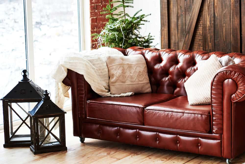 This is a close look at a brown leather chesterfield sofa by the glass window.
