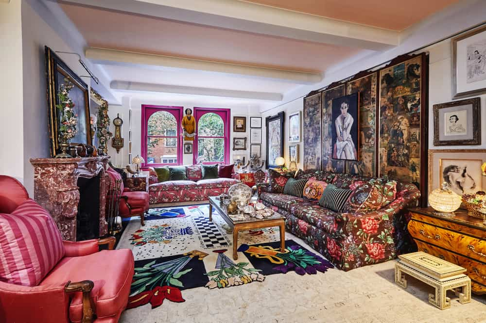 This is a full view of the apartment's living room that has a vintage fireplace, a large wooden coffee table and colorful patterned sofas adorned by various artwork. Image courtesy of Toptenrealestatedeals.com.