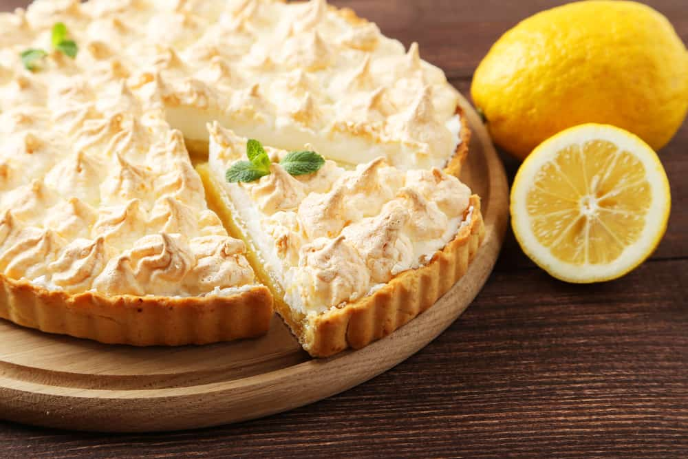This is a close look at a lemon meringue pie with fresh lemons on the side.