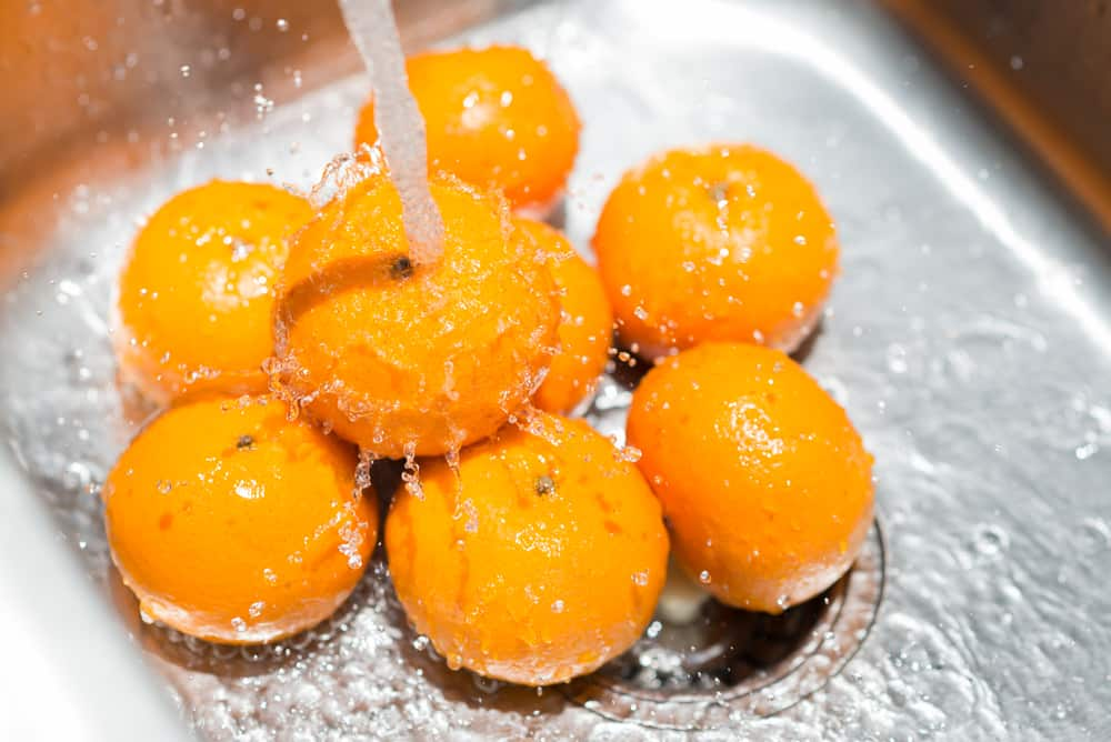 These are oranges being washed on the kitchen sink with the faucet on.