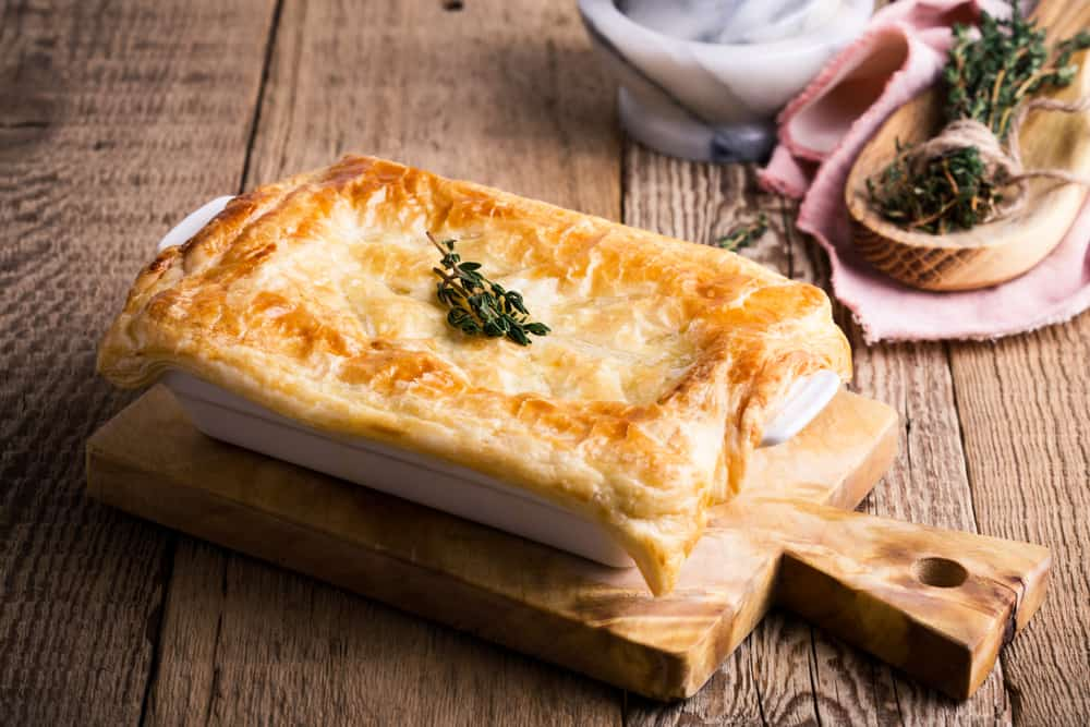 This is a freshly-baked puff pastry casserole on a wooden board.