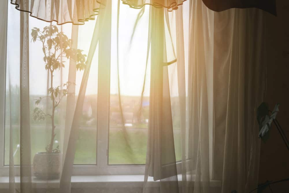 This is a window with window scarf of a white sheer curtain.