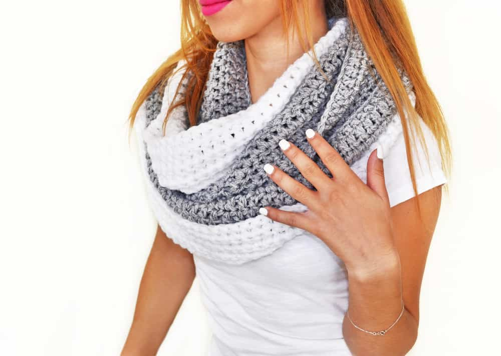 This is a woman wearing a knitted gray and white scarf on her neck.