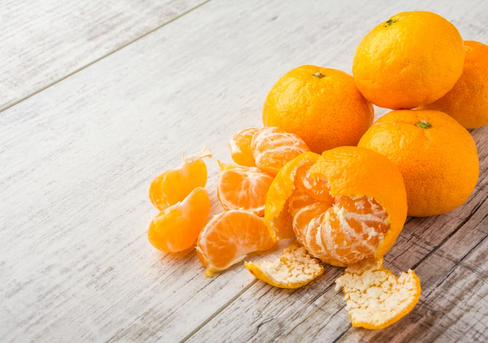 A couple of tangerines peeled on a wooden table.