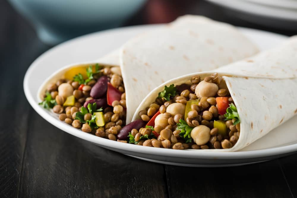 These are lentil burritos on a plate with chickpeas and beans.